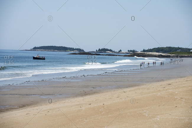 Georgetown, Maine, USA - June 26, 2016: People walking along the sandy beach at Reid State Park