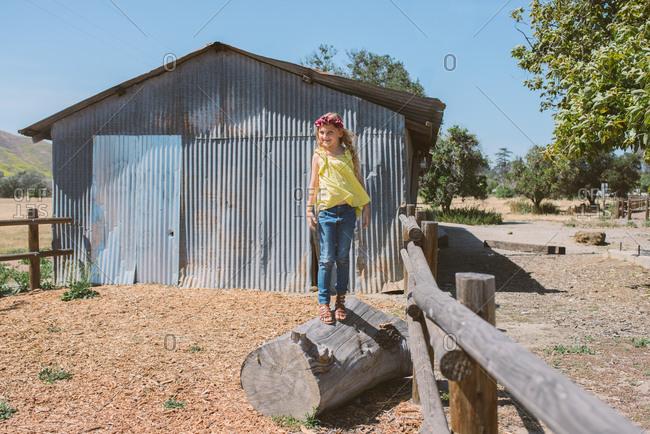 Girl standing on log