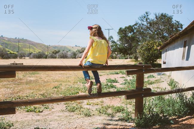 Girl sitting on wood fence