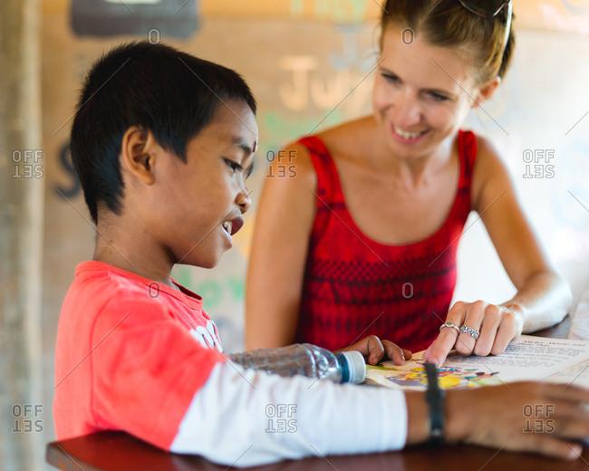 Siem Reap, Cambodia - April 1, 2015: Volunteer teacher engaging with student