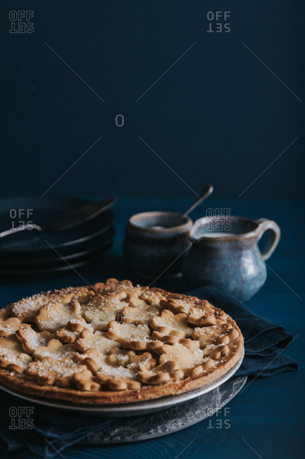 Apple pie with ceramics on blue background
