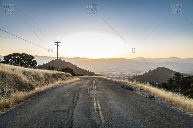 The sun rises in front of a road twisting it's way through the foothills of Sonoma County and Lake Sonoma, California.