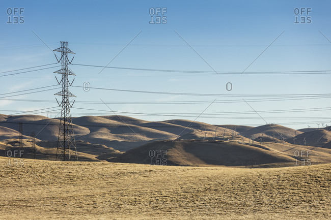 Wildmills and power lines in the Diablo Range of Northern California generating and transmitting green energy electricity.