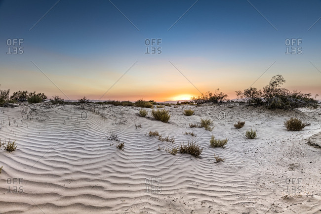 A setting sun over the sand dunes of the Mojave Desert.