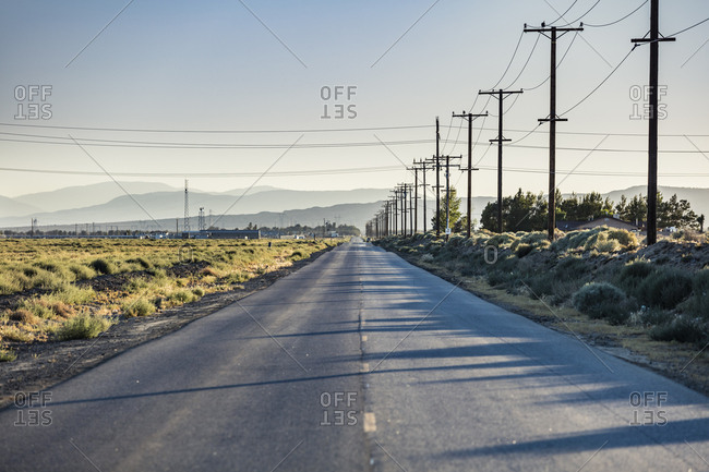 A road lined with telephone and power lines in the Mojave Desert of California.
