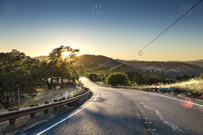 A road winds it's way through the mountains of Sonoma County at sunset in Northern California.