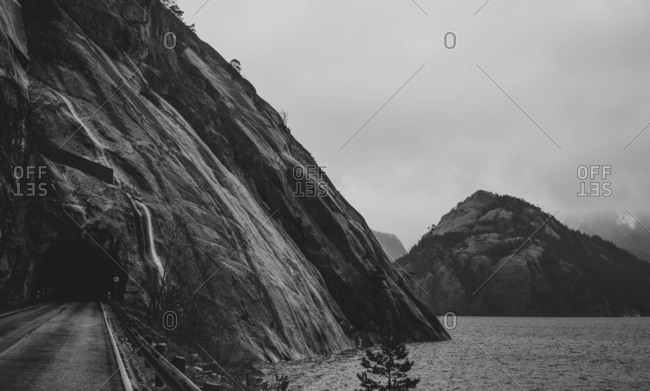 A road along the fjord going into a tunnel