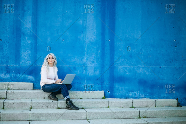 Young woman with white hair sitting by blue wall using a laptop in Barcelona, Spain