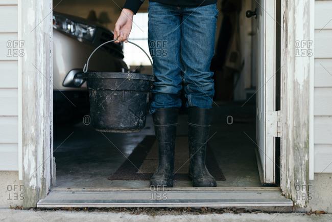 Boy standing in doorway holding bucket