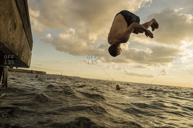 Young man diving into sea at sunset