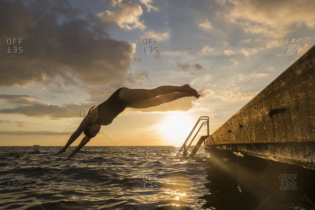 Woman diving into sea at sunset