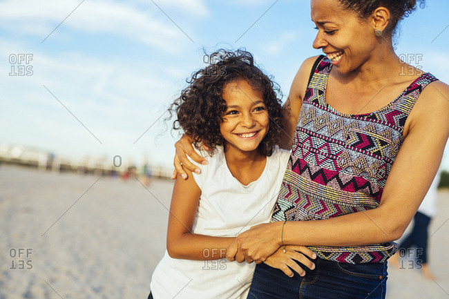 Mother embracing daughter (10-11) on beach