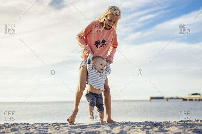 Older sister (8-9) teaching baby sister (6-11 months) to walk on beach