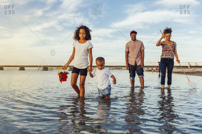 Parents with daughters (2-3, 10-11) wading in sea