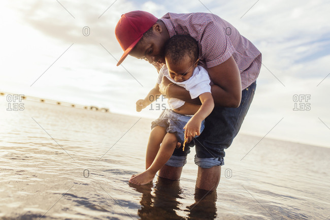 Father holding daughter (2-3) in sea