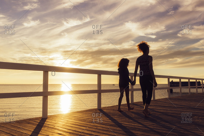 Mother and daughter (10-11) walking on wooden pier at sunset
