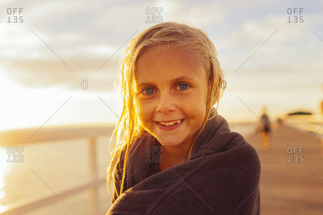Portrait of girl (8-9) in towel at sunset