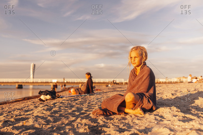 Girl (8-9) sitting on beach at sunset