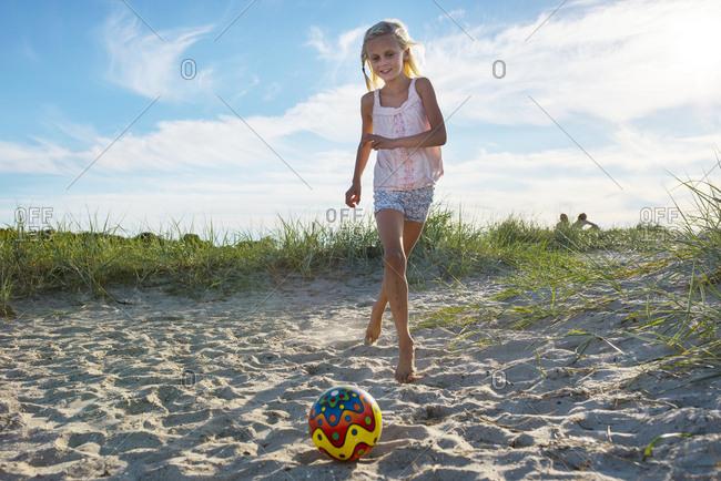 Girl (8-9) kicking ball on beach