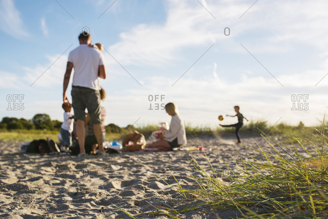 Two families picnicking together with children (6-11 months, 2-3, 4-5) on beach