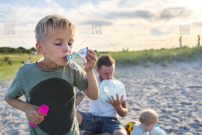 Father and children (6-11 months, 4-5) playing on beach
