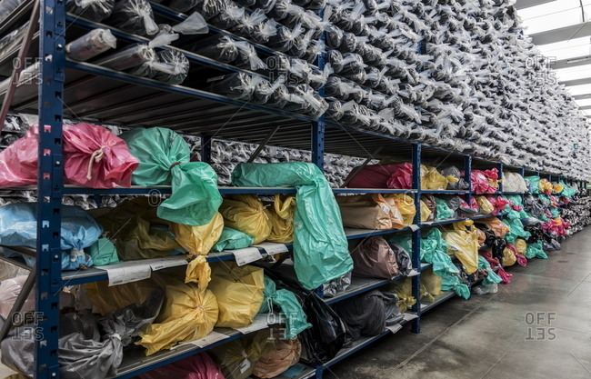 Valle Mosso, Italy - March 1, 2017: Shelves filled with bags in an Italian textile factory
