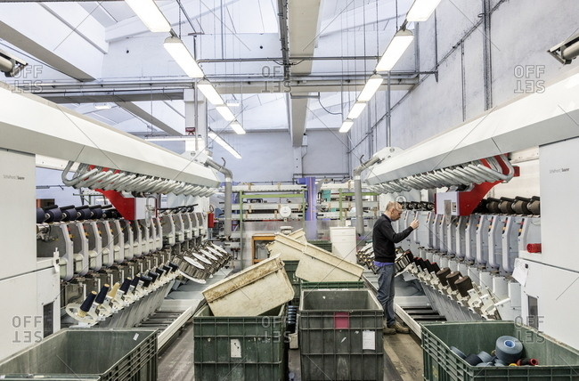 Valle Mosso, Italy - March 1, 2017: Man working machinery in an Italian textile factory