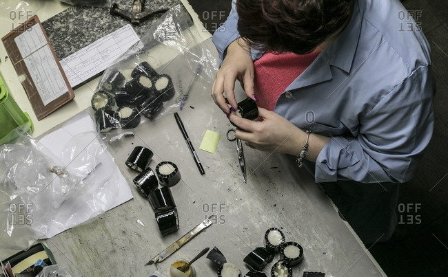 Lomazzo, Italy - November 24, 2016: Overhead view of woman inspecting heels for shoes in a factory