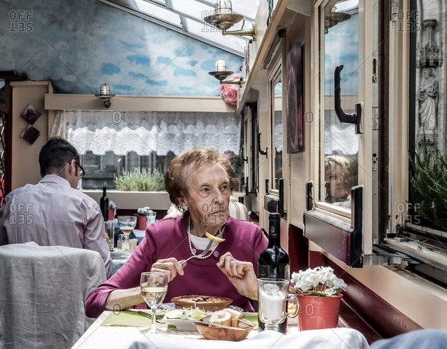 Antwerp, Belgium - August 6, 2016: Senior woman eating Sunday lunch in a restaurant
