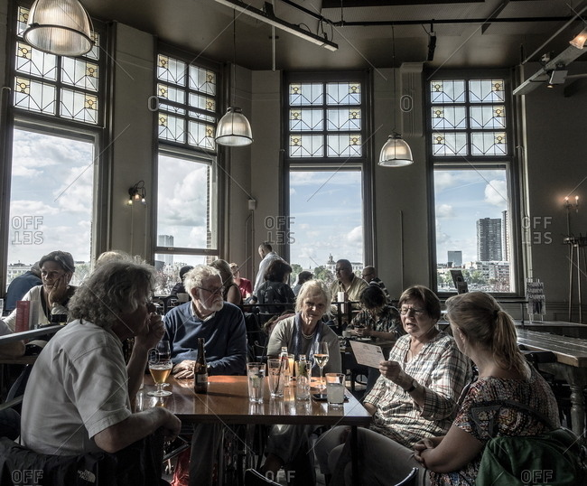 Rotterdam, Netherlands - August 8, 2016: Group of people having drinks at the Hotel New York bar in Rotterdam, Netherlands