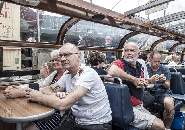 Amsterdam, Netherlands - August 14, 2016: People on a boat cruising the canals of Amsterdam