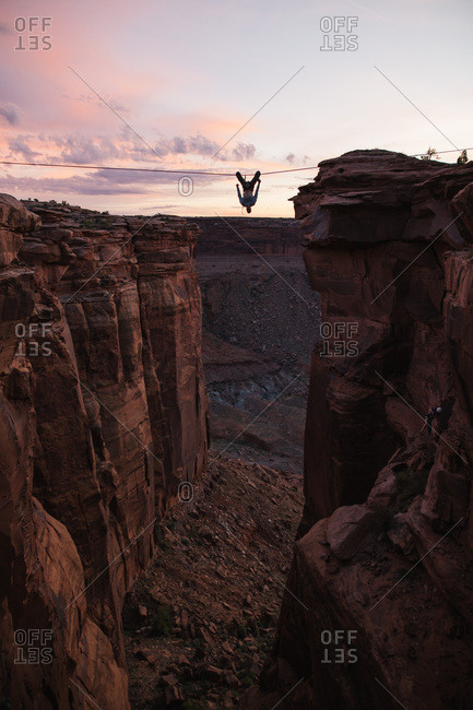 Person hanging from line over gorge