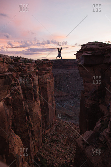 Person hanging from tightrope over canyon