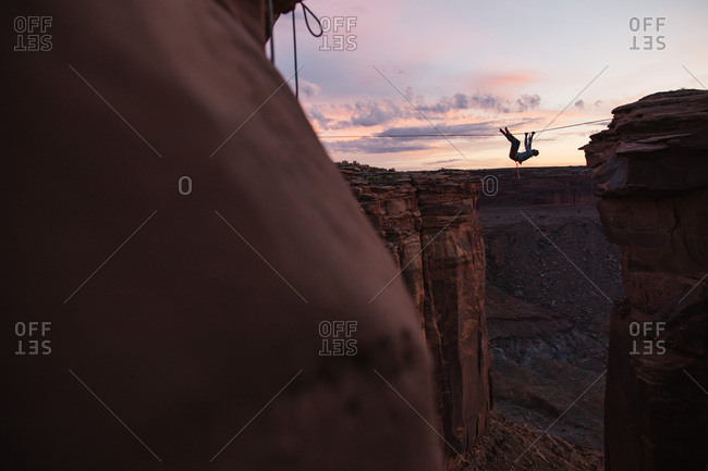 Person climbing tightrope over canyon