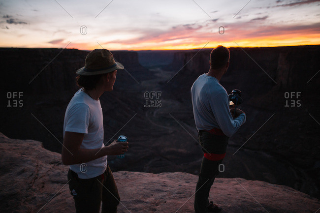 Two men watching sunset over canyon