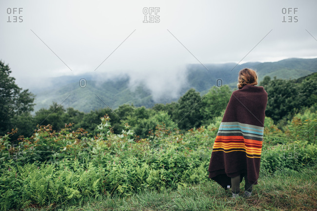 Woman in blanket overlooking mountains