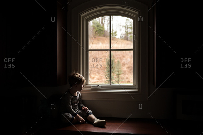 Young boy sitting on floor and gazing out window