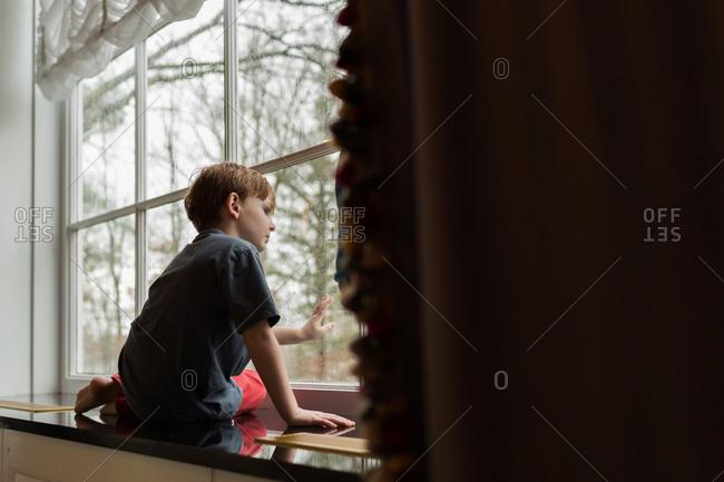 Boy sitting on window ledge and gazing outside