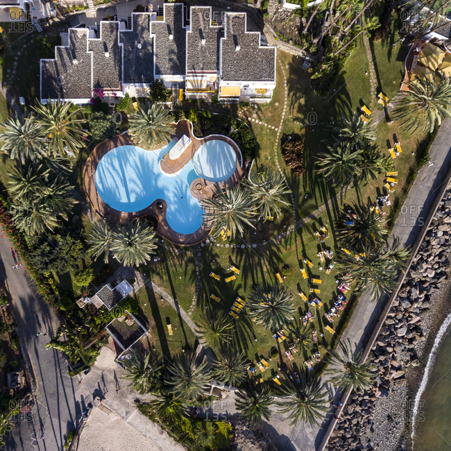 Gran Canaria, Spain - November 10, 2016: Aerial view of palm trees and a swimming pool at a seaside resort