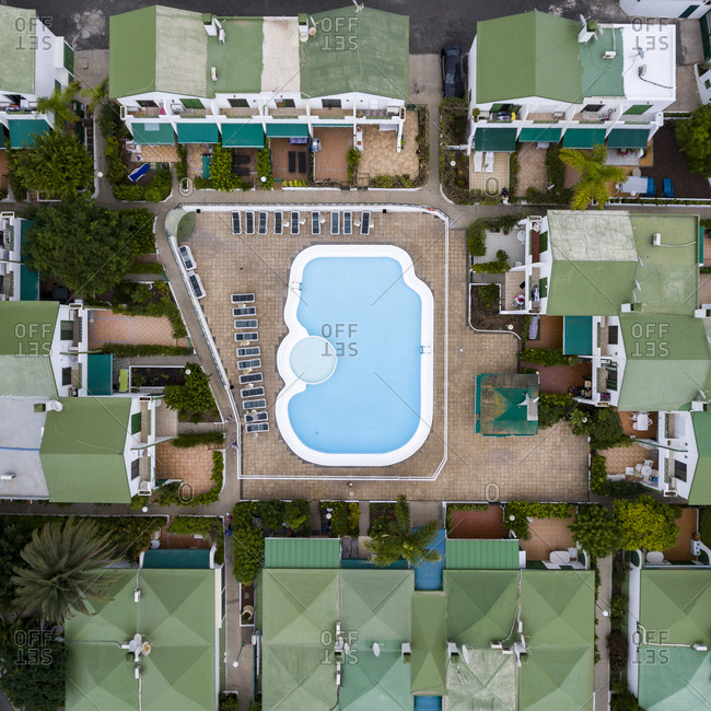 Maspalomas, Spain - November 21, 2016: Aerial view of a swimming pool between buildings with green rooves