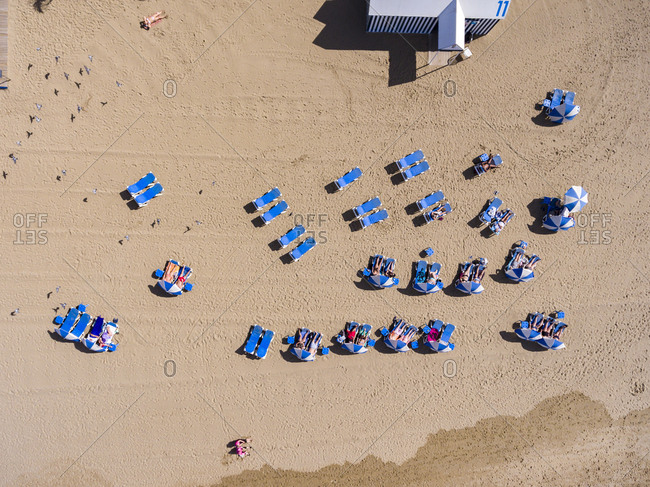 Las Palmas, Spain - November 23, 2016: Sunbathers in lounge chairs on a sandy beach