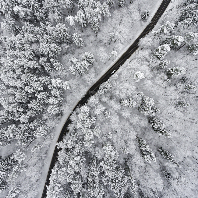 Aerial view of a highway winding through a frozen forest