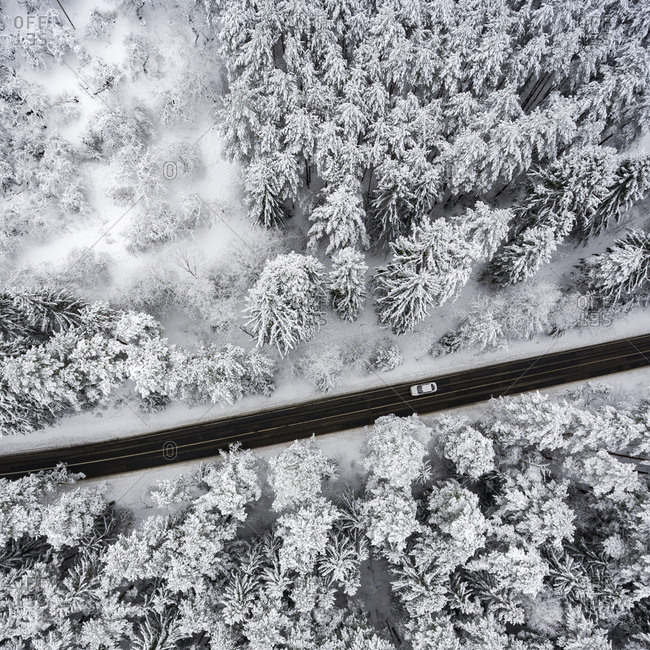 Aerial view of a road cutting through a snow-covered forest