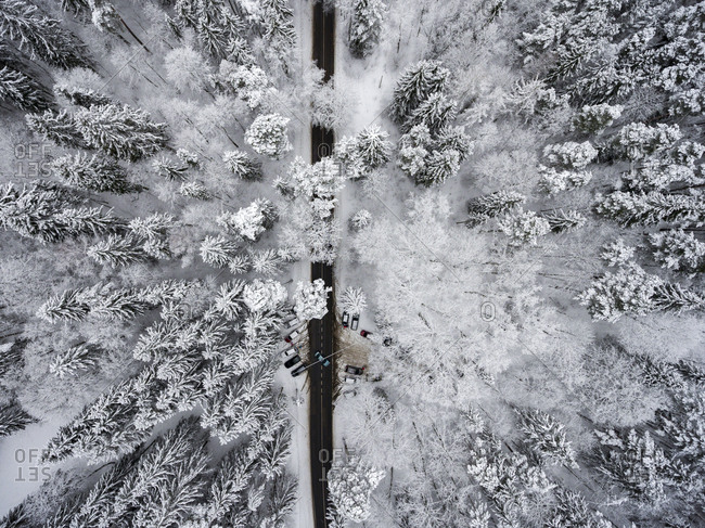 Aerial view of cars parked beside a highway in a frozen forest