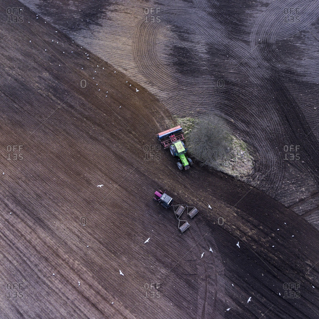 Aerial view of two tractors plowing a farm field