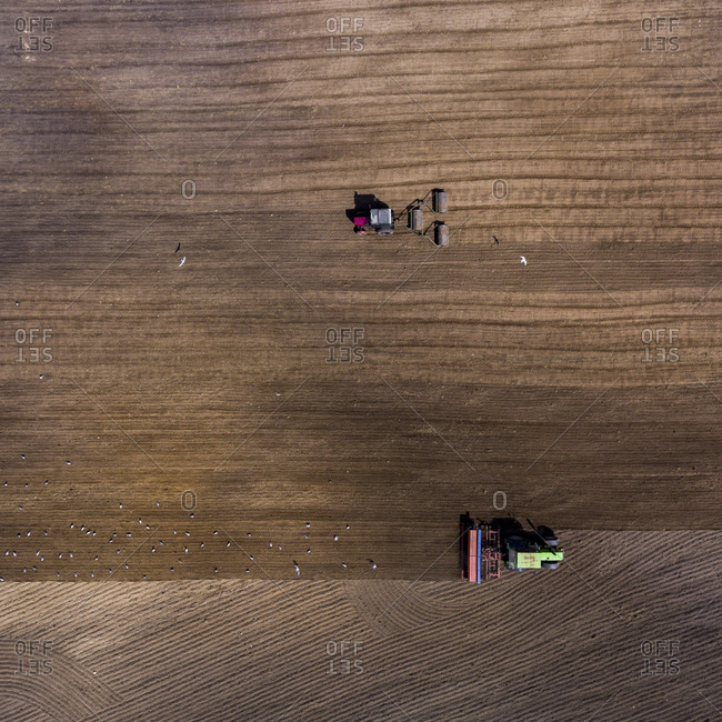 Aerial view of two tractors plowing lines in a rural field