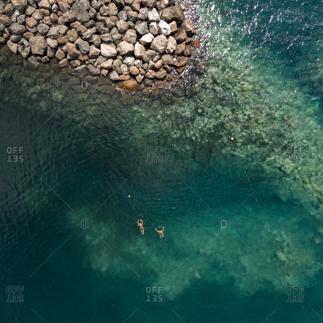 Aerial view of swimmers in a lagoon near a rocky coast