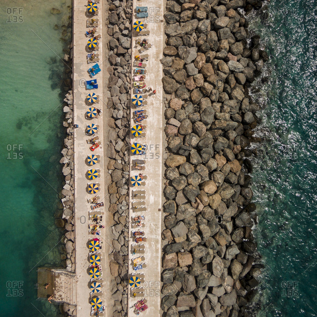 Aerial view of colorful umbrellas on a strip of rocks and sand by a seaside