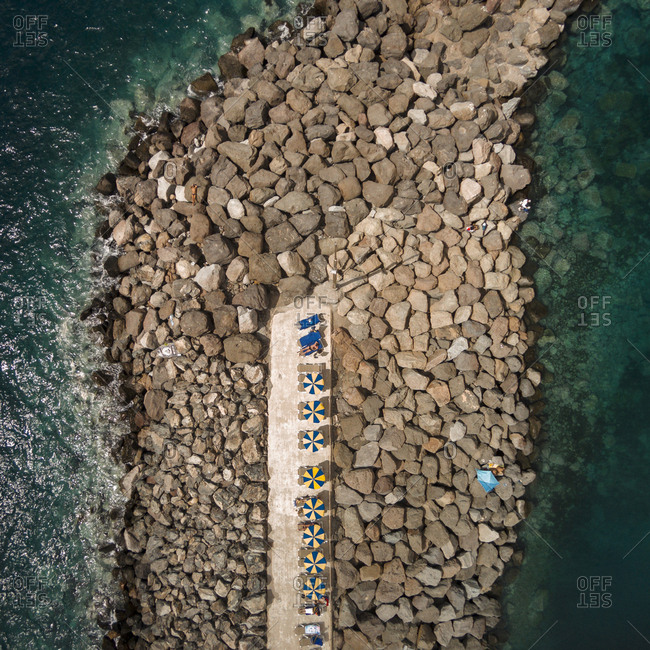 Aerial view of umbrellas on a rocky strip overlooking a lagoon at a resort