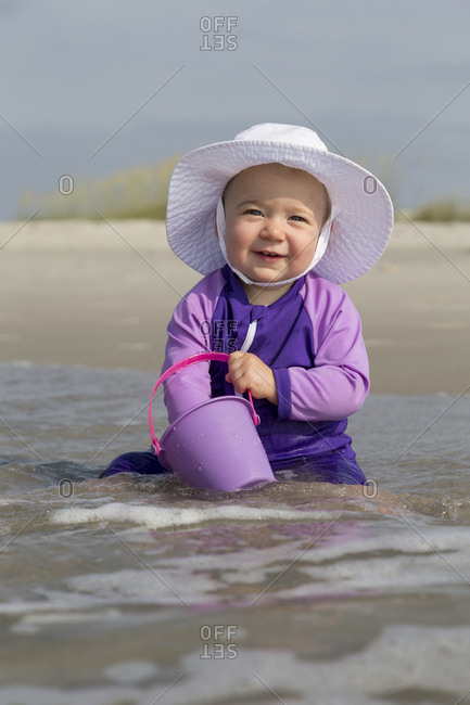 A young girl plays on a beach with plastic pail